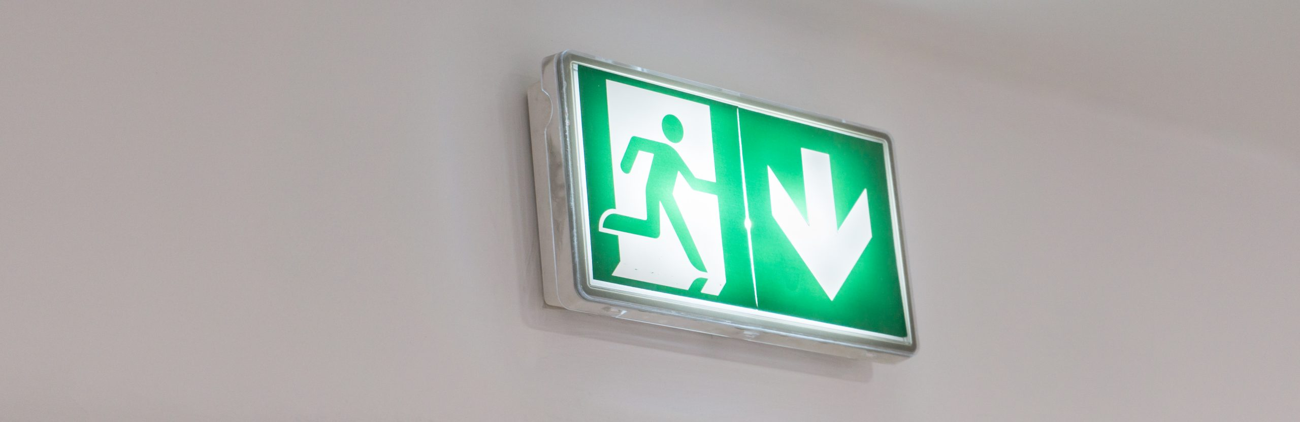 Emergency,Exit,Sign,In,A,Building,Glowing,Green